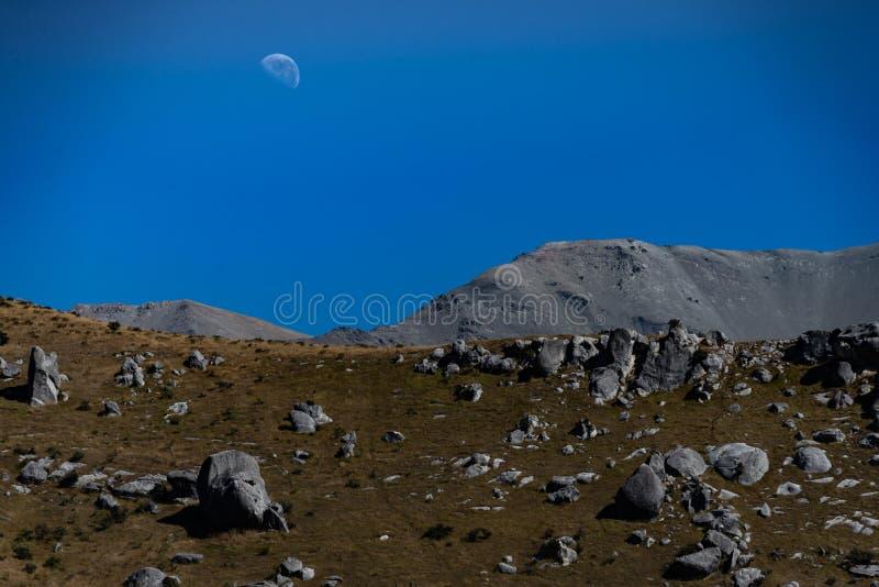 Maan in hemel boven rotsachtig maanachtig landschap stock foto
