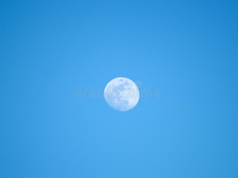 Maan in het vierde kwartaal op een blauwe hemel stock foto