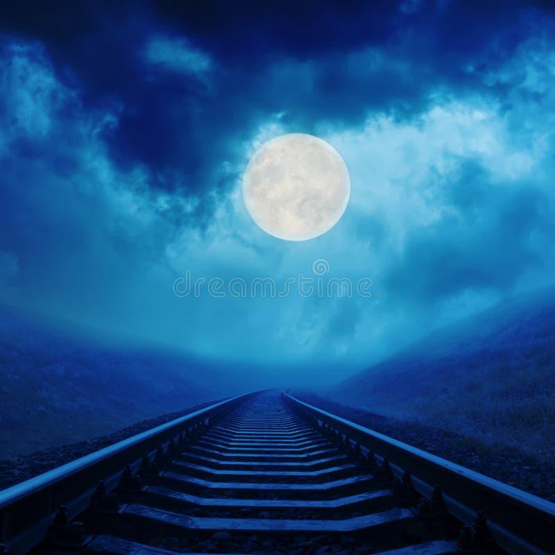Maan in nachtwolken over spoorweg stock foto