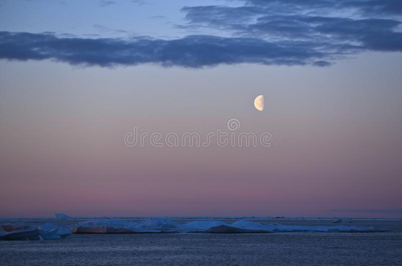 Maan over ijsgebieden in het noordpooloverzees stock foto
