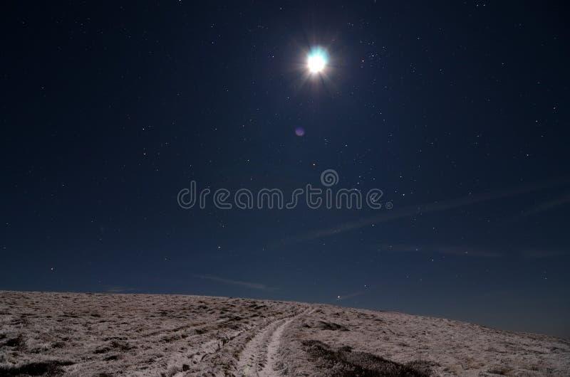 Maan over sneeuwweg royalty-vrije stock afbeelding
