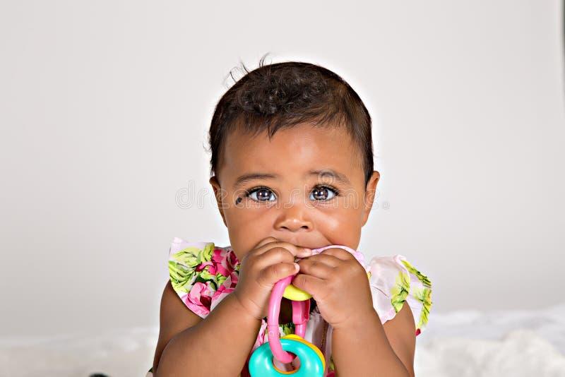 7 maand het oude baby kauwen op plastic stuk speelgoed royalty-vrije stock foto's