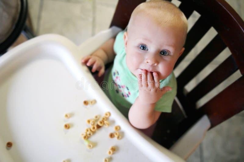 6 maand Oude Baby die als Hoge Voorzitter Ontbijtgraangewas eten stock afbeeldingen