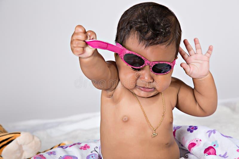 7 maand oude baby die zonnebril proberen op te stijgen stock fotografie