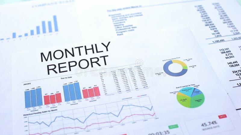Maandelijks rapport die over lijst, grafiekengrafieken en diagrammen, officieel document liggen stock foto