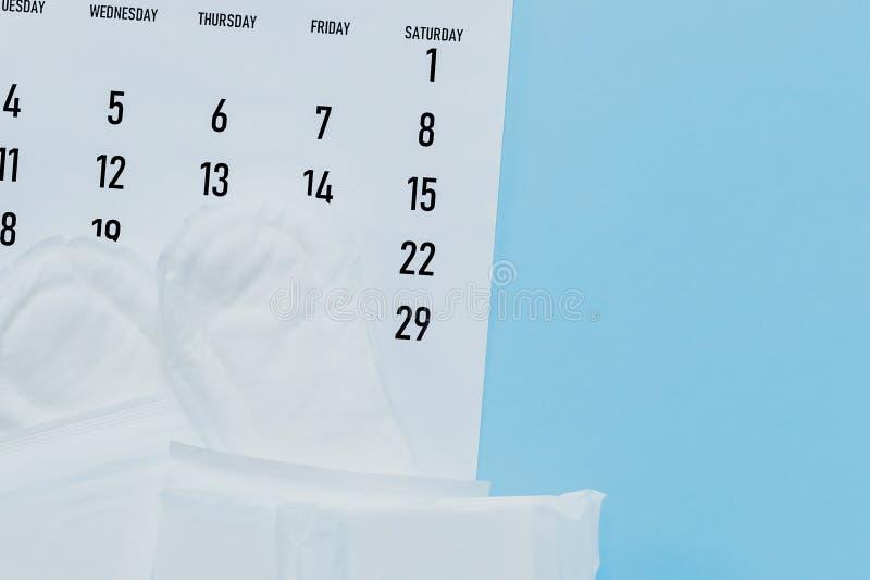 Maandelijkse kalender en sanitaire stootkussens De kalender van de menstruatiecyclus Het concept van de vrouwengezondheid Het con royalty-vrije stock afbeelding