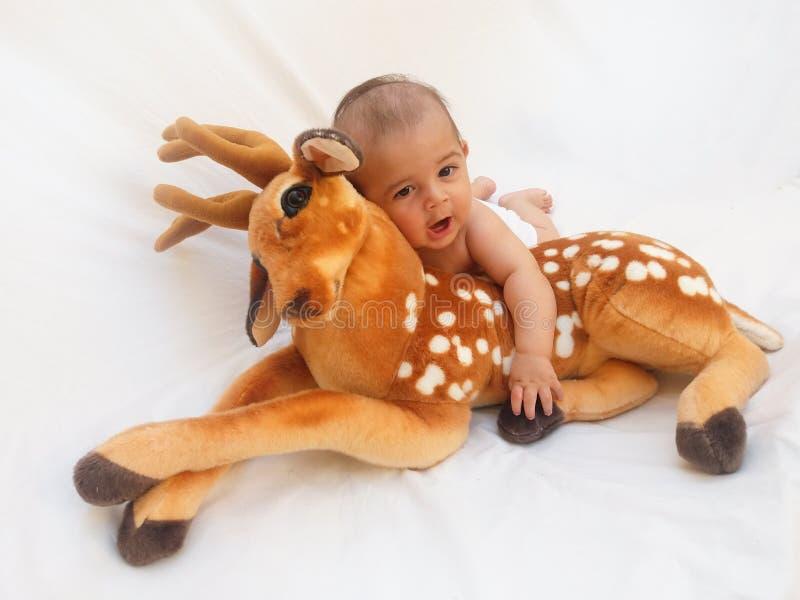 4 maanden oud babyjongen het spelen met zacht beste stuk speelgoed en kuiken stock foto