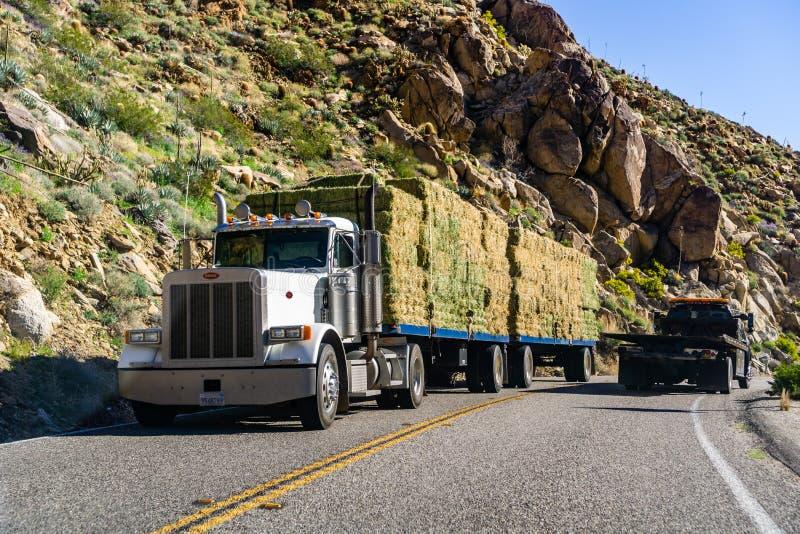 18 maart, 2019 Borrego springt/CA/de V.S. - Vrachtwagen die bailes van hooi door de bergen vervoeren op stock foto's