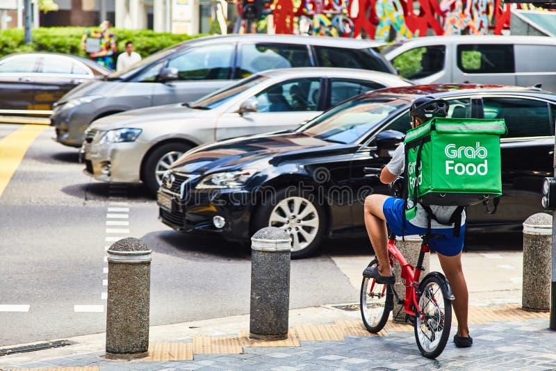 19 maart, 2019 - Singapore: Koerier voor levering van voedsel 'Greep 'op een fiets in Singapore stock afbeelding