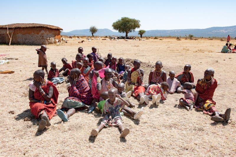 Maasai部落的马塞人人、妇女和孩子坐地面,坦桑尼亚,非洲 免版税库存图片