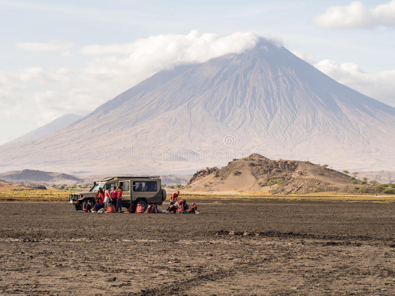 Maasai in Arusha. Maasai people selling their products to a tourist group in the dry part of Lake Natron. Ol Doinyo Lengai active volcano in the background royalty free stock photo