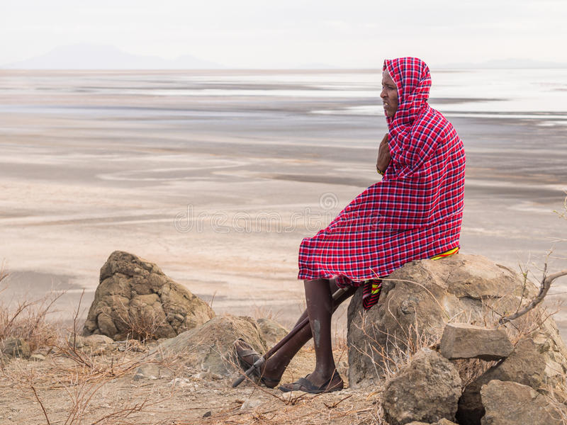 Maasai in Arusha. Maasai warrior wearing traditional red clothes rests on a rock in the dried part of Lake Natron in the North of Tanzania, Africa stock photos