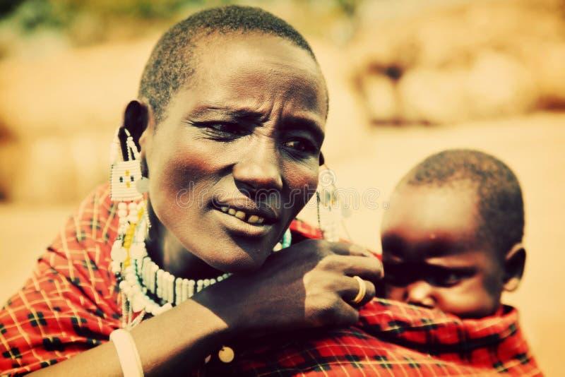 Maasai baby carried by his mother in Tanzania, Africa. Maasai village, TANZANIA, AFRICA - DECEMBER 11: Maasai crying baby carried by his mother on December 11 stock photo