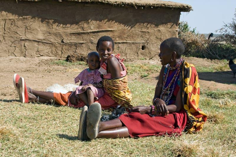 Maasai kobiety z niezidentyfikowanym dzieckiem odpoczywają przed błoto budującą budą obrazy stock