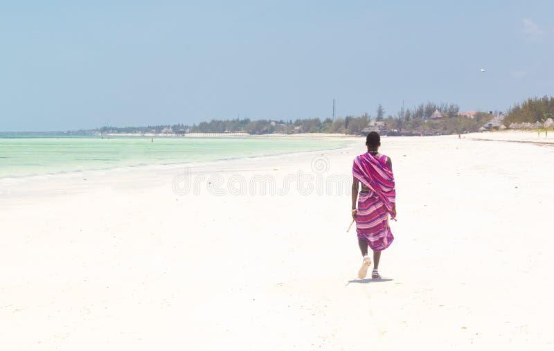 Maasai krigare som går på den perfekta tropiska sandiga stranden för bild Paje Zanzibar, Tanzania royaltyfri foto