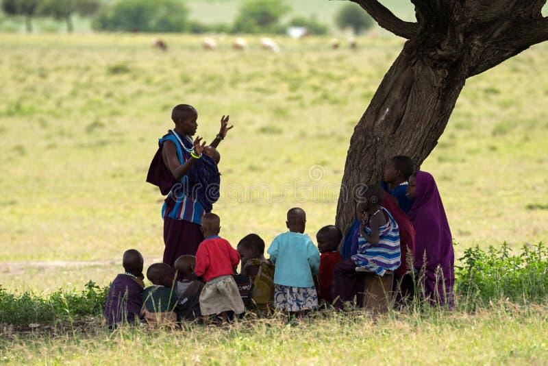 Maasai kvinna, lärarinna som undervisar unga afrikanska ungar som sitter i skugga av under-akaciaträdet i Tanzania, Afrika royaltyfri bild