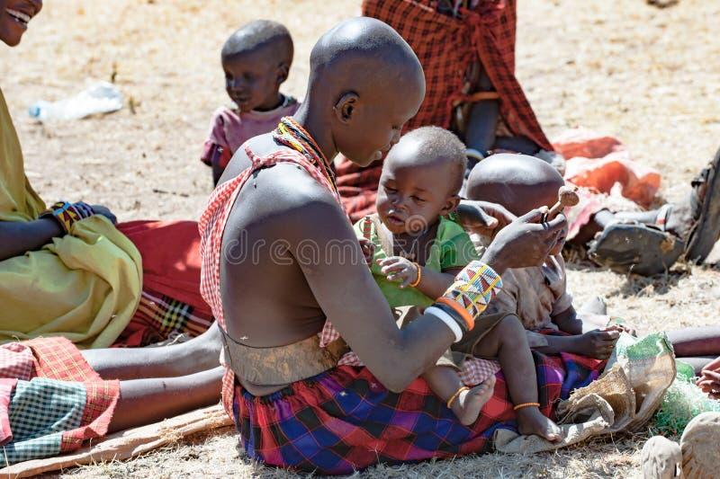 Maasai-Mutter, die mit Baby, Tansania spielt stockbild