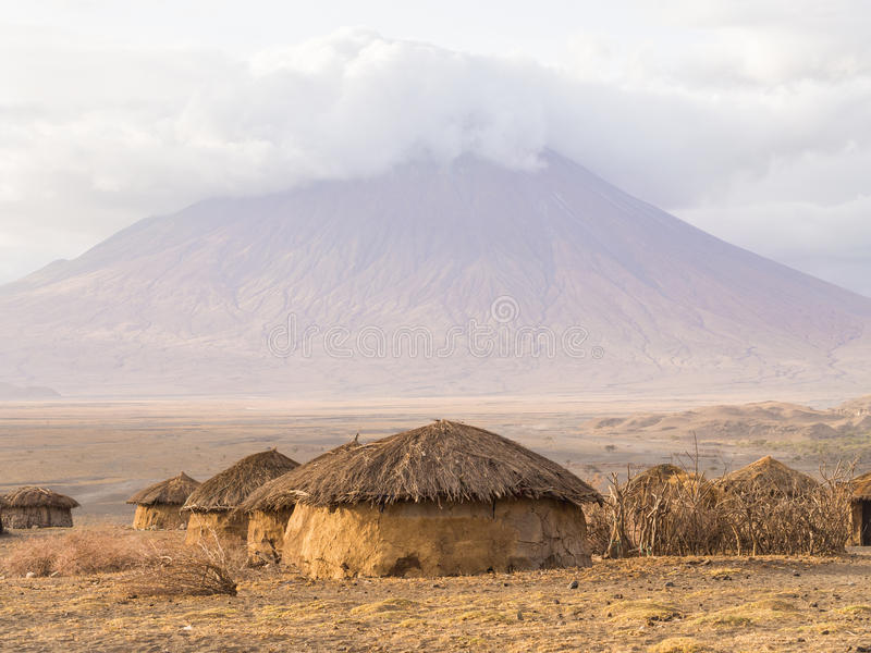 Maasai vilage in Africa. Maasai village in front of the Ol Doinyo Lengai (Mountain of God in the Maasai language), an active volcano in Arusha Region in the royalty free stock image