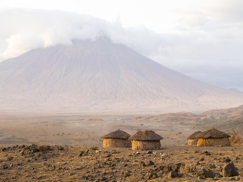 Maasai village in Arusha. Maasai village in front of the Ol Doinyo Lengai (Mountain of God in the Maasai language), an active volcano in Arusha Region i the stock photos