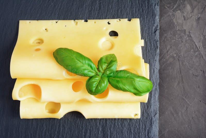 Maasdam与新鲜的蓬蒿的乳酪切片 库存图片