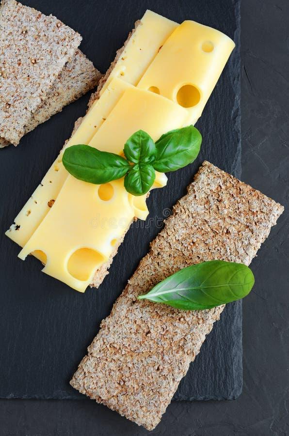 Maasdam在薄脆饼干的乳酪切片与新鲜的蓬蒿 库存图片