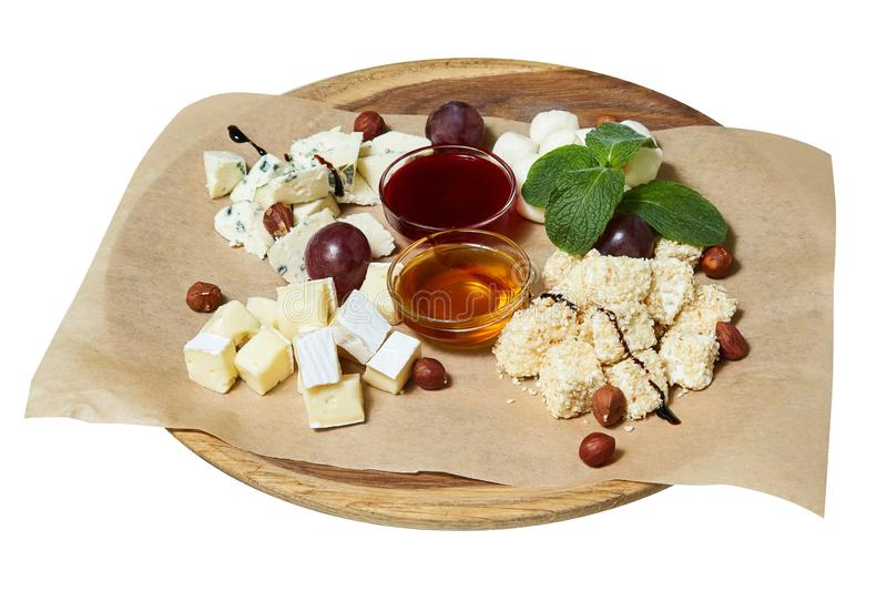 Maasdam, brie, camembert, roquefort cheeses on cheese board served with grapes royalty free stock photos