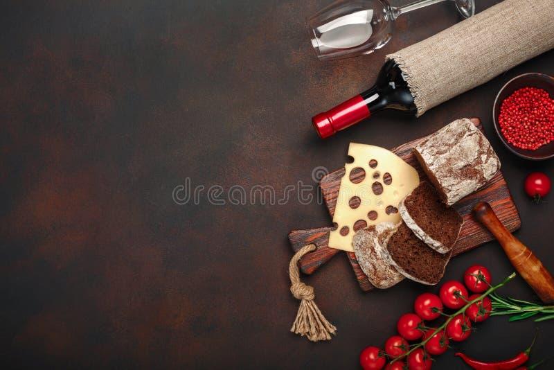 Maasdamkaas op een scherpe raad met kersentomaten wordt gesneden, zwart brood, knoflook en rozemarijn, fles wijn, wijnglas dat royalty-vrije stock afbeelding