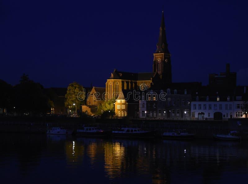 Maastricht på natten, den holländska staden på floden Maas med fartyg royaltyfria bilder