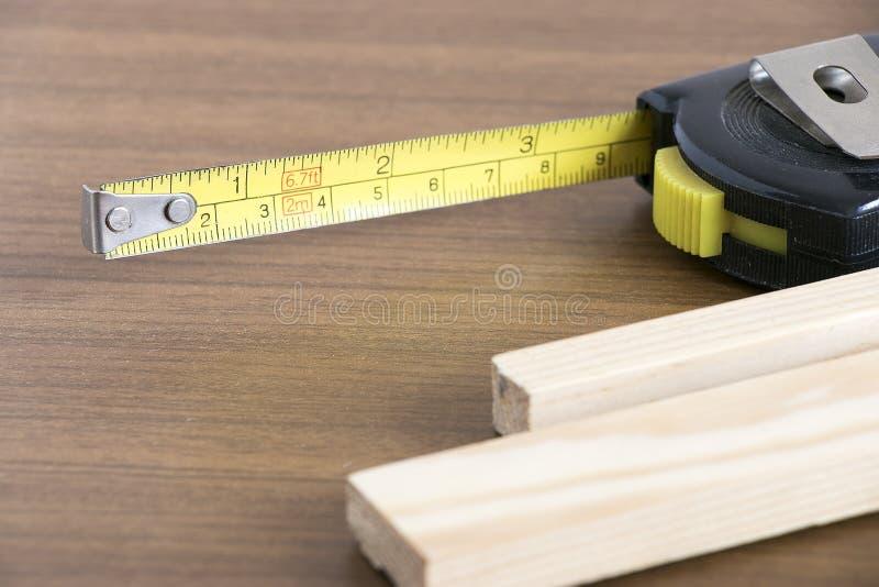 Maatregelenband en hout stock fotografie