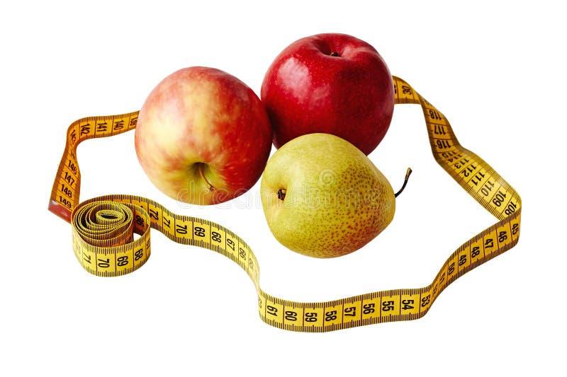 Maatregelenband en vers die fruitappelen en peer over witte achtergrond worden geïsoleerd Verliesgewicht, slank lichaam, gezonde  stock fotografie
