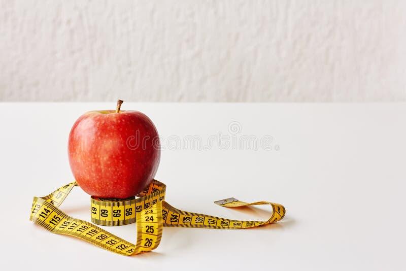 Maatregelenband en vers fruitappel op witte achtergrond Verliesgewicht, slank lichaam, gezonde voedingconcept stock fotografie