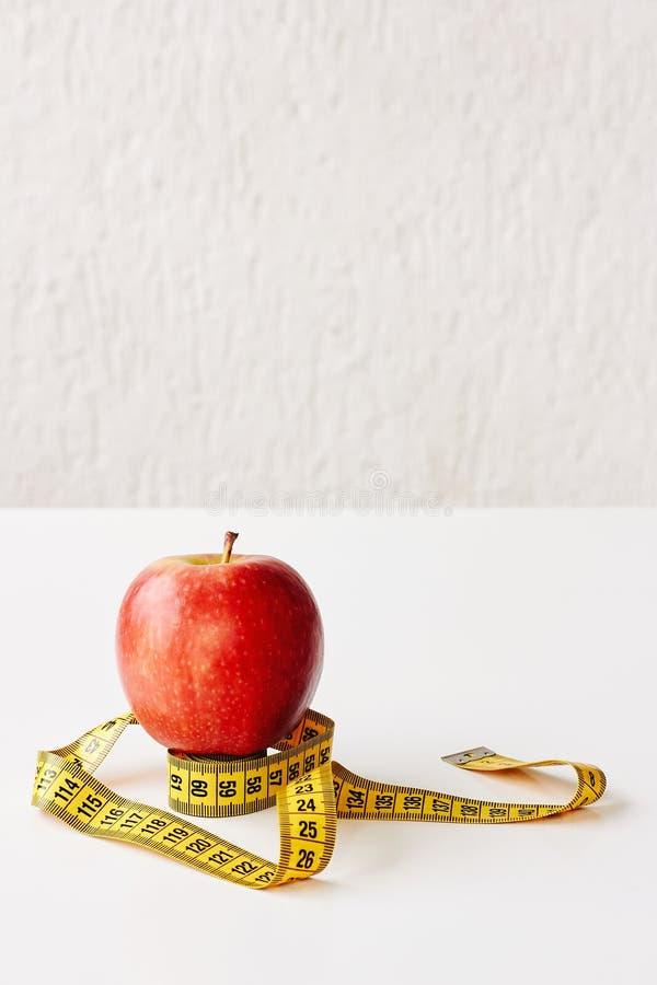 Maatregelenband en vers fruitappel op witte achtergrond Verliesgewicht, slank lichaam, gezonde voedingconcept royalty-vrije stock fotografie