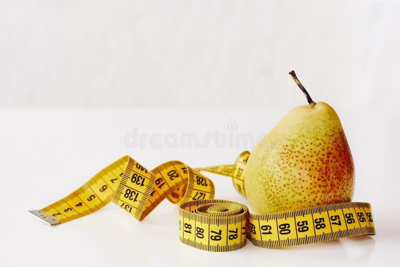 Maatregelenband en vers fruitpeer op witte achtergrond Verliesgewicht, slank lichaam, gezonde voedingconcept royalty-vrije stock fotografie
