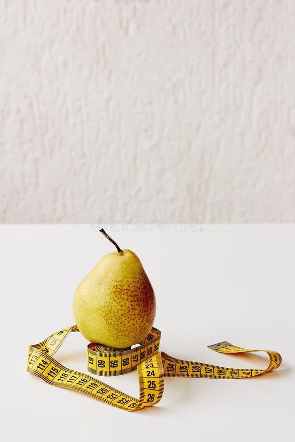 Maatregelenband en vers fruitpeer op witte achtergrond Verliesgewicht, slank lichaam, gezonde voedingconcept stock foto's
