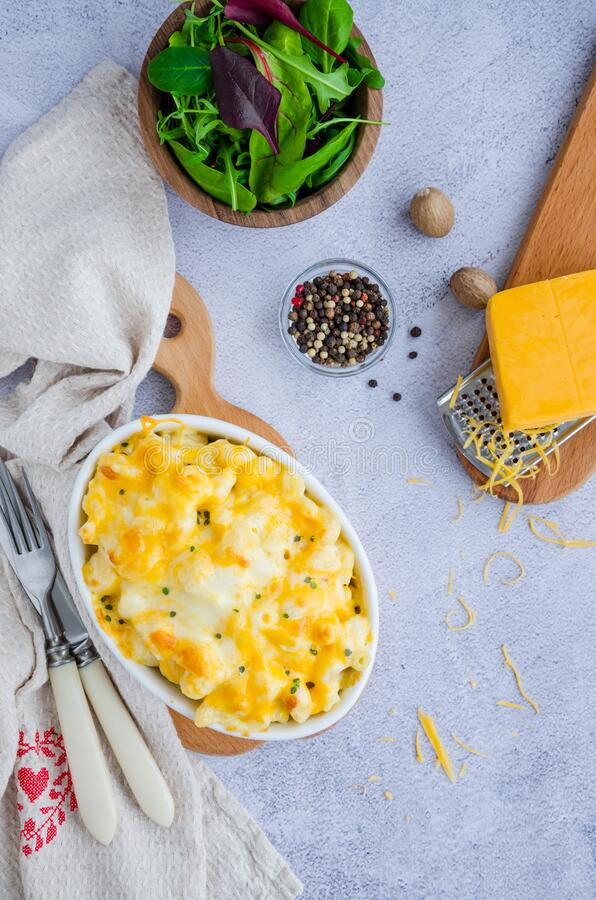 Mac and cheese. Traditional baked macaroni with cheese in baking form. American cuisine. Vertical orientation. stock photo
