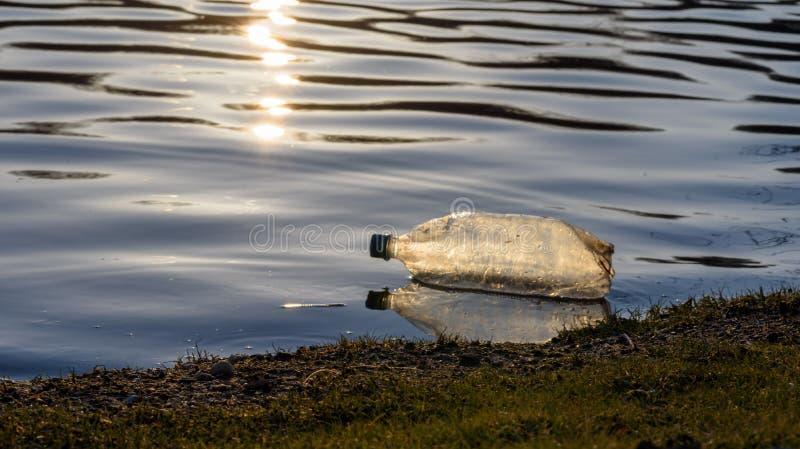 Maca plástica da garrafa de água que flutua no lago no por do sol fotografia de stock royalty free