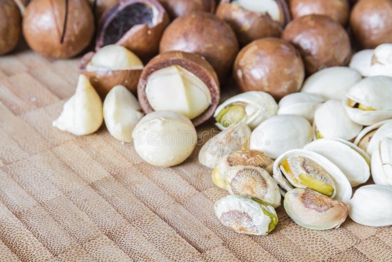 Macadamia en Pistachenoot op houten lijst stock afbeelding