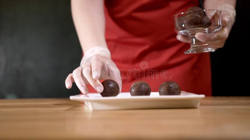 Macadamia nuts on plate. Action. Close-up of woman in apron puts three macadamia nuts on sample on black isolated stock image