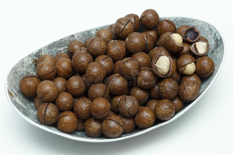 Macadamia nuts in silver bowl on white background top view stock photos