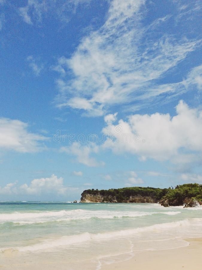 Macao beach against stormy Atlantic ocean. And sky in clouds and rocks with cliff. Sky is blue, water is not calm stock image