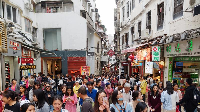 Macao, China - Feb. 9, 2019: Crowd of people and tourists that walking on the shopping market alley near St. Paul Church ruins stock photo