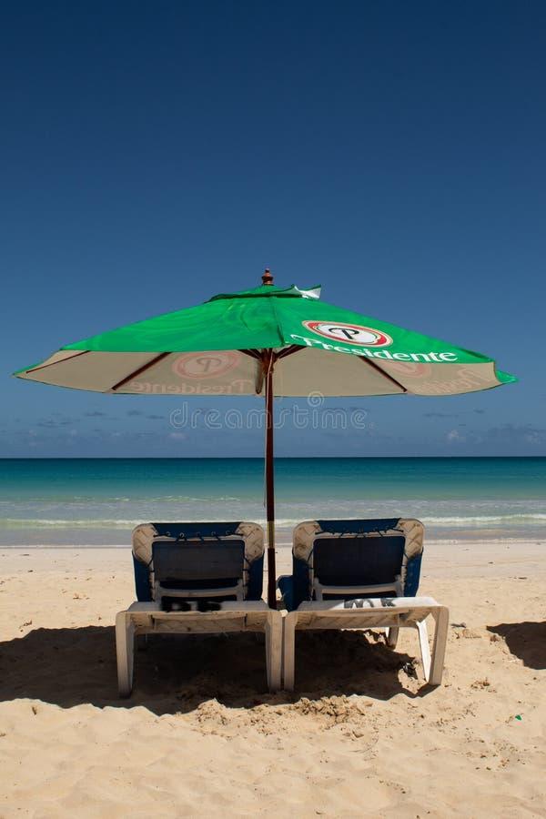 Macao strand, Bavaro, Dominikanska republiken, 10 april, 2019/en dag på den offentliga stranden, med typiska sunbeds, paraplyer,  arkivfoton