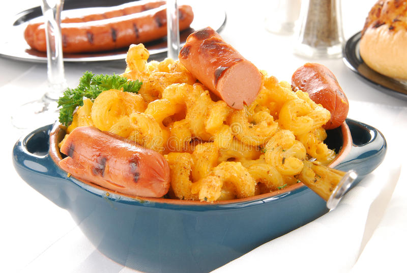 Macaoni and cheese with hot dogs. A crock of gourmet baked macaroni and cheese with hot dogs stock images