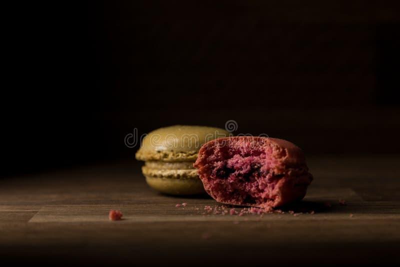 Macaron с меткой укуса, пинком и зеленым Macarons на деревянном столе, завтраке в свете утра стоковая фотография rf