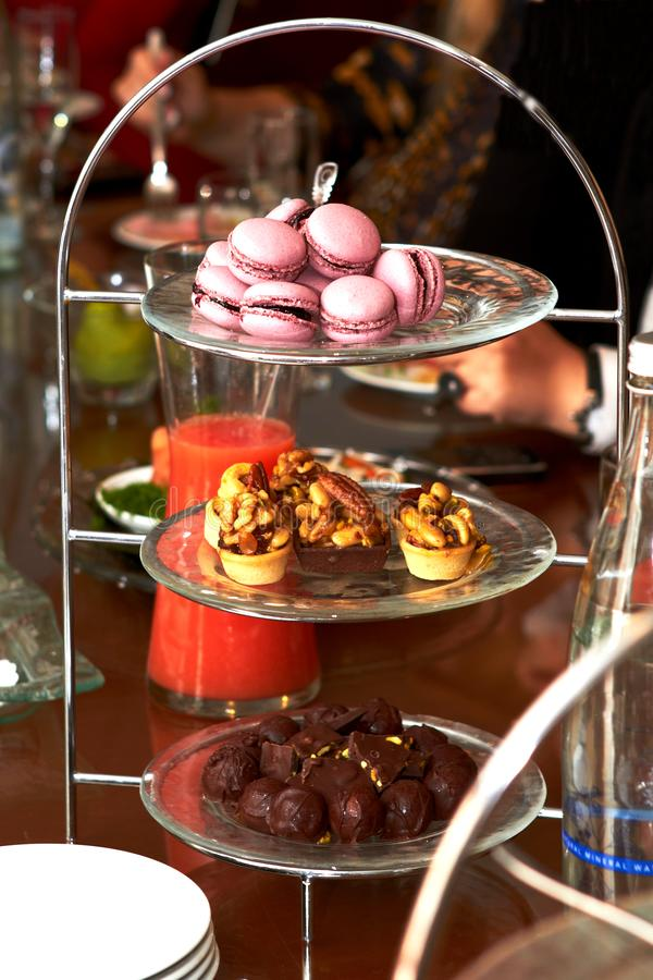 macaron, basket cakes and chocolates lying on a special stand stock image