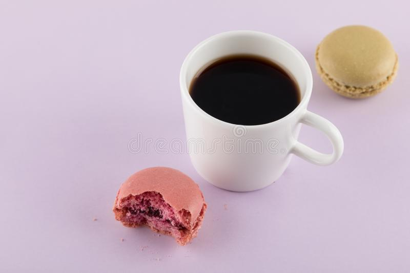 Macaron with bite mark and Coffee,Pastel colors, purple background. Tasty and Beautiful Macaron with bite mark and Coffee, Pastel colors, purple background stock photography