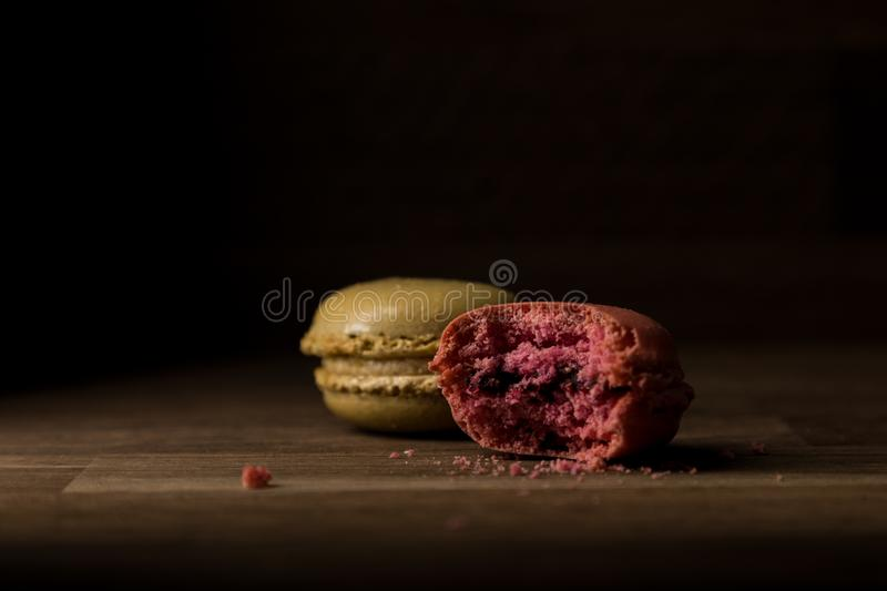 Macaron with bite mark, Pink and Green Macarons on wooden table, breakfast in morning light. Beautiful Macaron with bite mark, Pink and Green Macarons on wooden royalty free stock photography