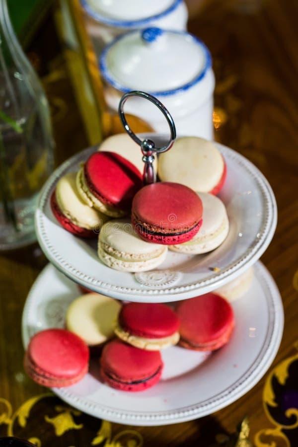 Macaron branco e cor-de-rosa no cakestand contra o fundo do recipiente imagens de stock