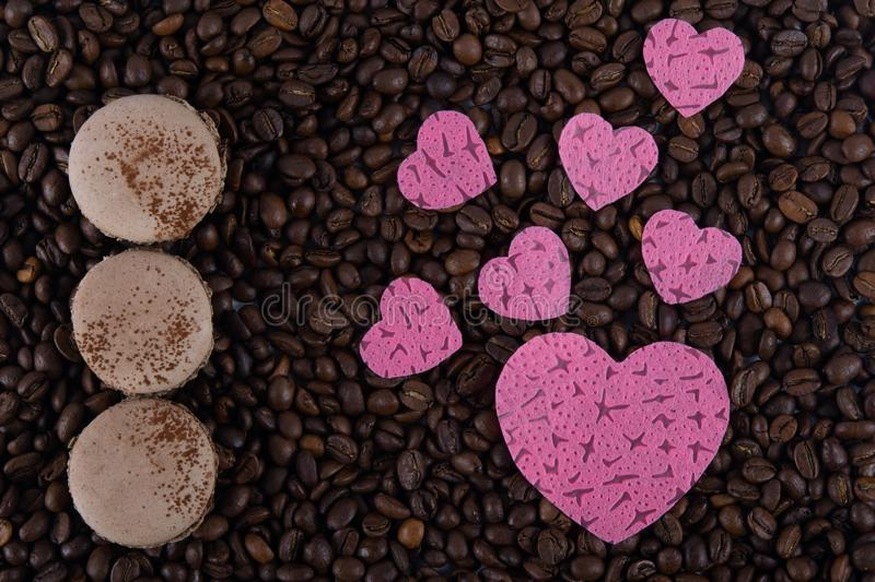 Macaron coffee cookies on arabica grains and pink hearts stock image