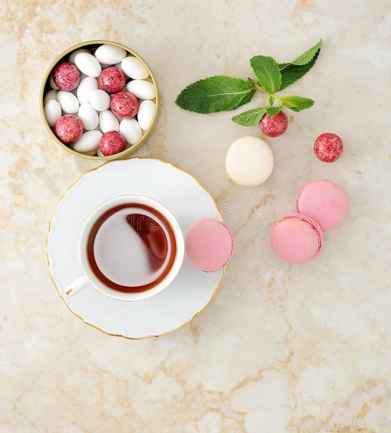 Macaron colorido con una taza de té foto de archivo
